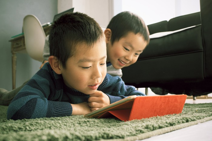 Two kids looking at a tablet screen.