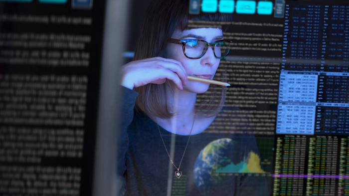 An IT worker looks at a computer screen.