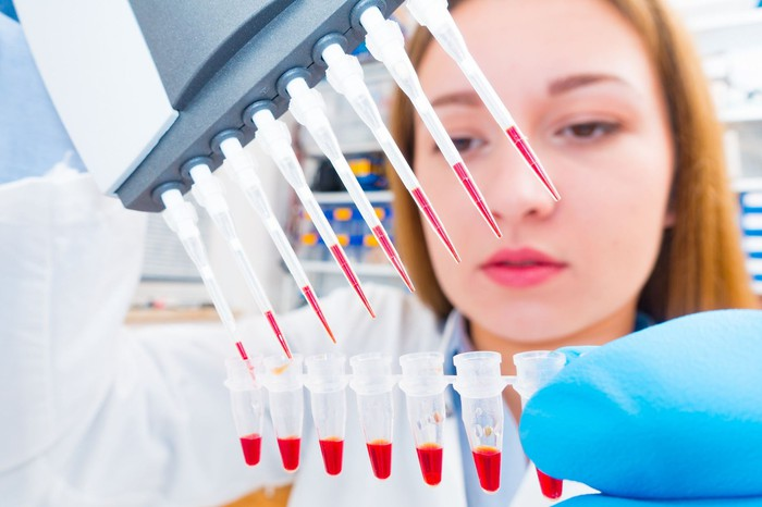 A lab technician using a multi-pipette device to fill a row of test tubes with red liquid.
