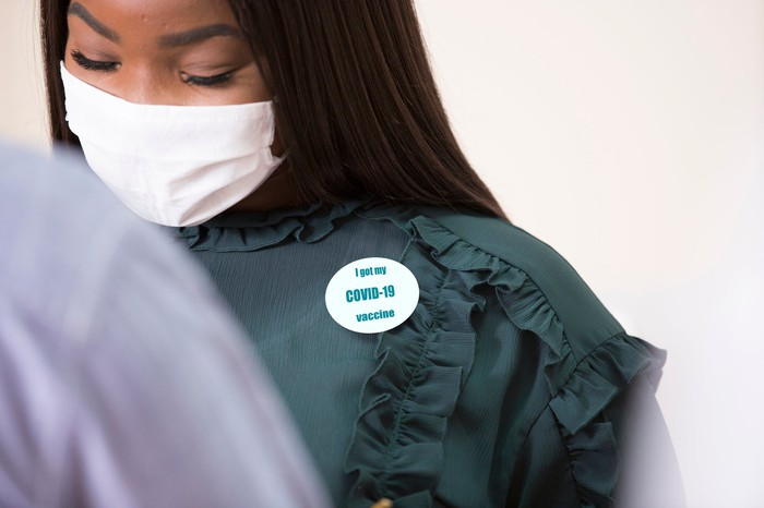 """A masked person wearing an """"I got my COVID-19 vaccine"""" badge."""