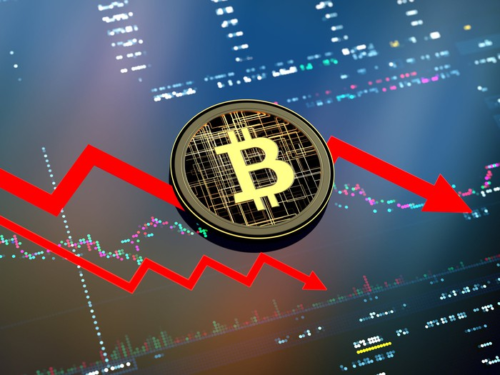Artist's rendering of a Bitcoin overlaid on a falling stock chart
