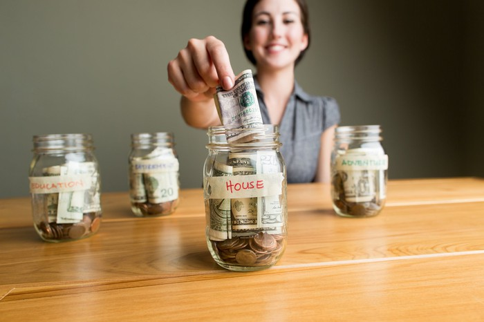 A person putting money into one of four savings jar for large purchases like a house.