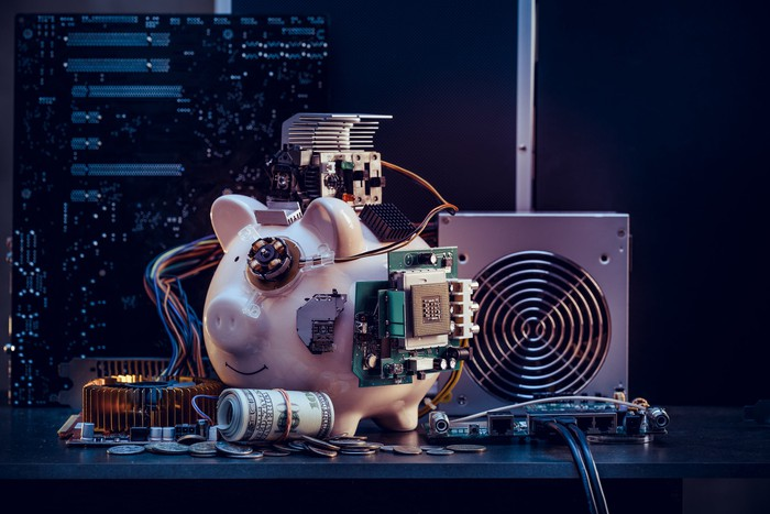 Piggy bank surrounded by computer components and cash.