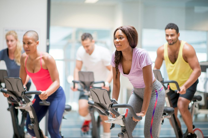A group of people on exercise bikes.