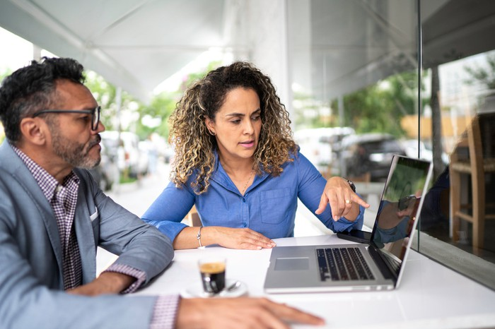 two business people looking at data on computer screen