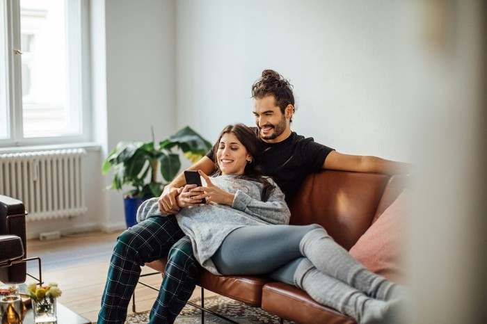 Two people on couch using smartphone.