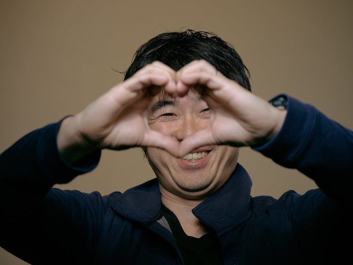 Man making a heart shape with his hands.