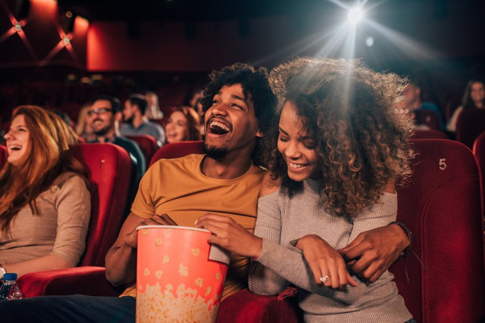 A couple in a theater laughing and eating popcorn.