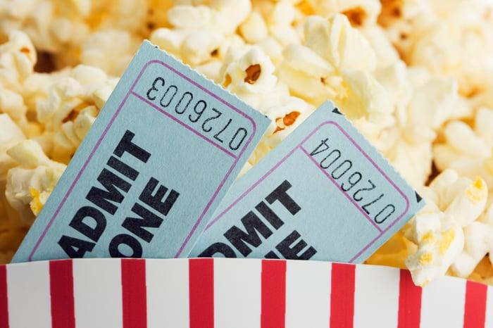Dos boletos de entrada al cine colocados en un cubo lleno de palomitas de maíz en un puesto de venta.