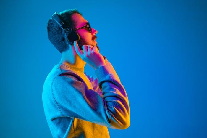 Person listening to headphones.