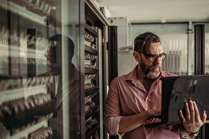 Mature adult works in a data center while holding a laptop.