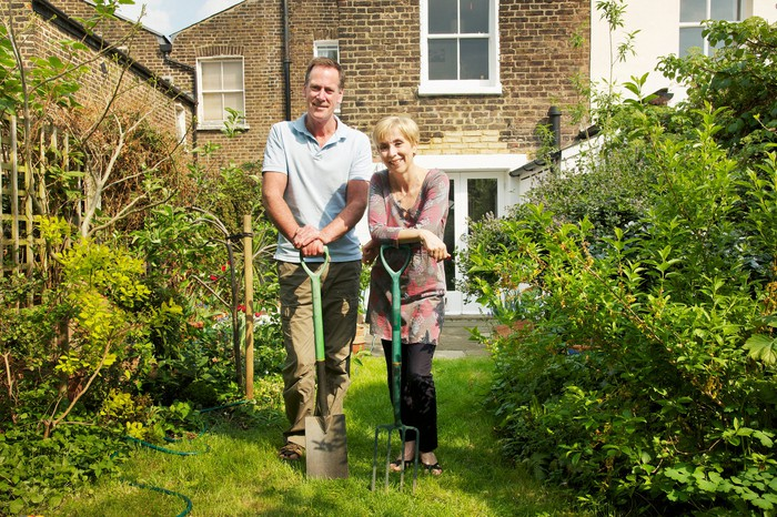 A couple holds shovels in a garden, with a brick house behind them.