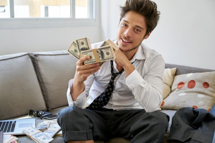 A disheveled man sits on a sofa with piles of money.