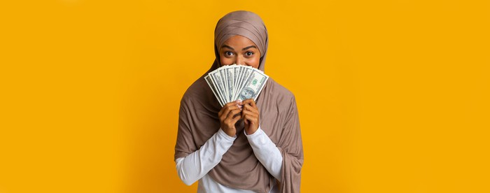 A person is holding fanned out money in front of half her face.