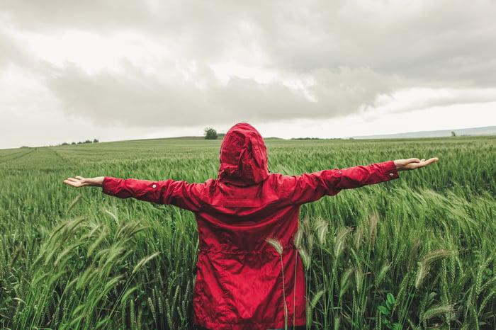 Une personne vêtue d'une veste rouge debout dans un champ, les bras tendus, alors qu'une tempête s'abat.