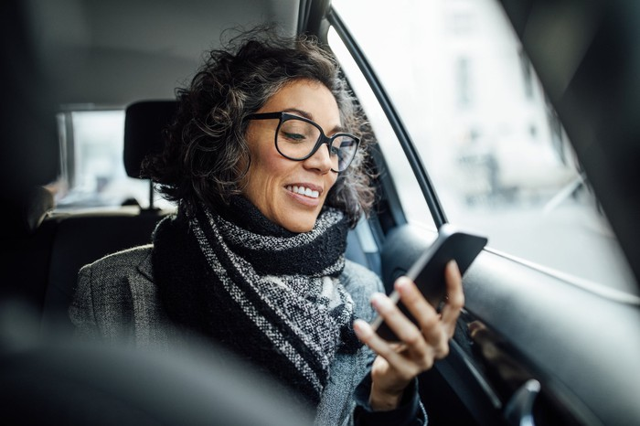 A woman sitting in a car and looking at her phone.