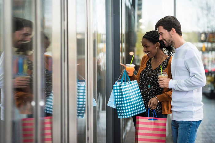 A man and woman holding shopping bags and looking at a store window.