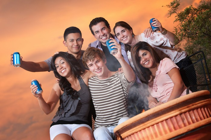 A group of teenagers drinking canned soda.