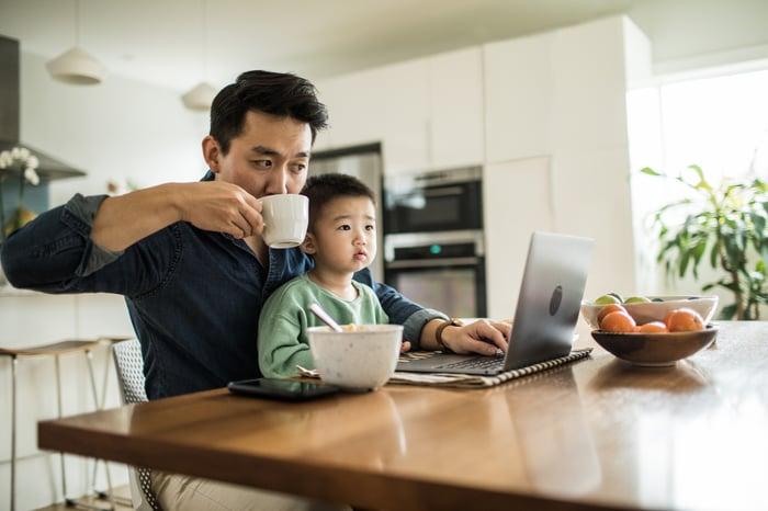 Le père travaille sur un ordinateur portable à la table du petit-déjeuner avec son jeune fils sur les genoux.