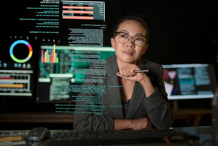 Une ingénieure en logiciel regarde un écran translucide avec des graphiques et des données dessus dans une pièce sombre.