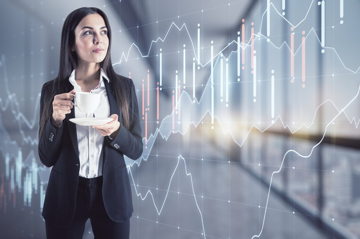 Investor holding a coffee cup while she looks at financial trend lines.