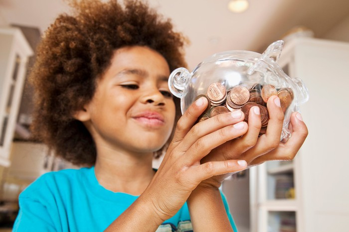 A child holds a glass piggy bank filled with pennies.
