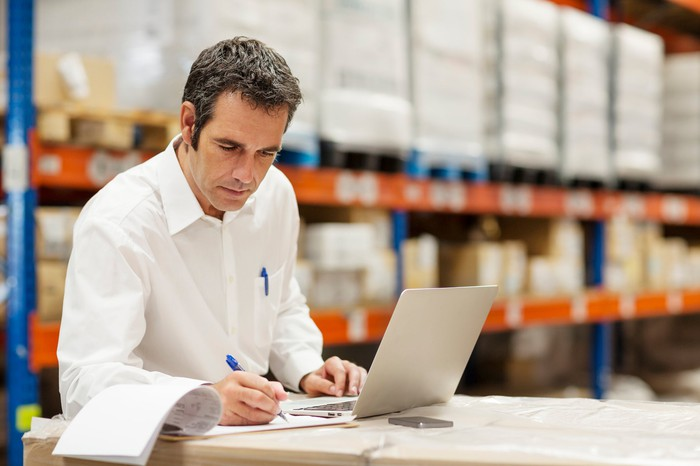 A person in a warehouse using a laptop and writing on a clipboard.