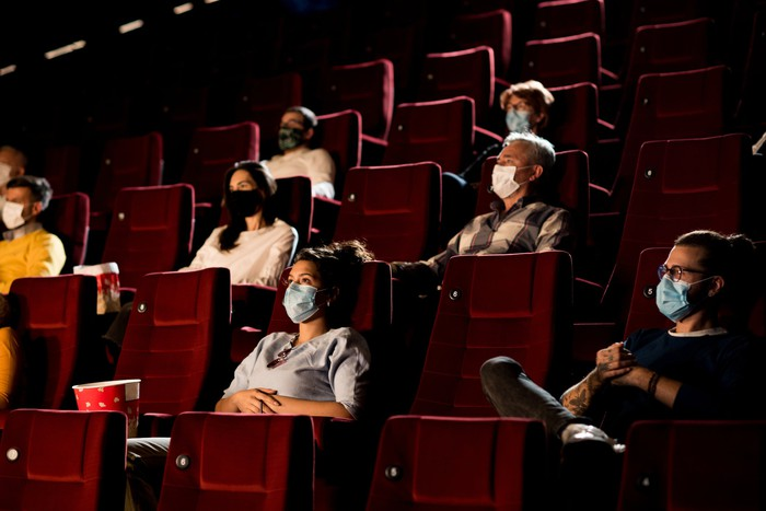 People wearing social distancing masks in theater