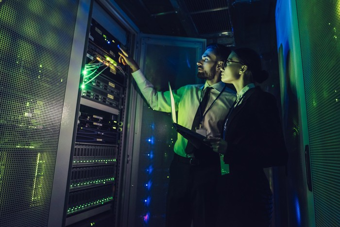 Two people looking at computer servers.