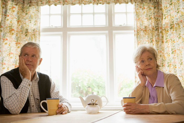 Two older people sitting at a table with their heads in their hands.