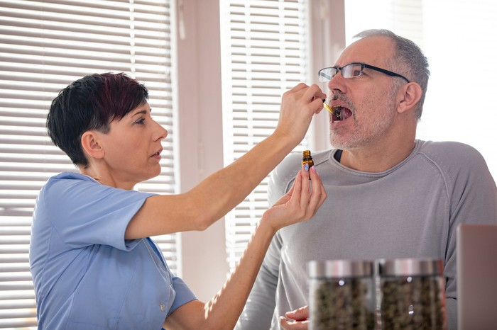 Technician administering CBD oil to patient.