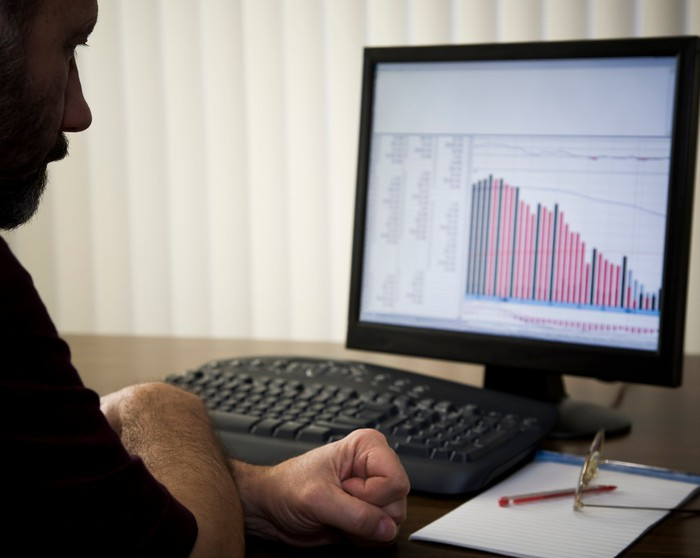 A man looking at a chart on a screen.