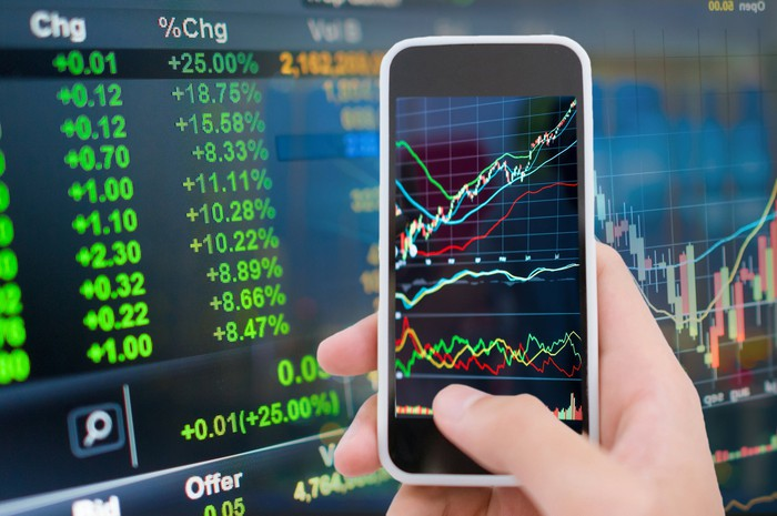 A person analyzing rising stock price charts on a smartphone with a stock price display board in the background.