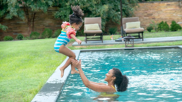 Young child jumping into a pool into the waiting arms of an adult.