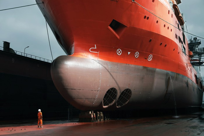Worker staring up at the prow of a very large ship in drydock