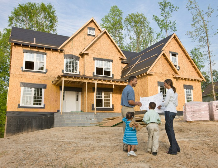 A family stands in front of their new house which is under construction.