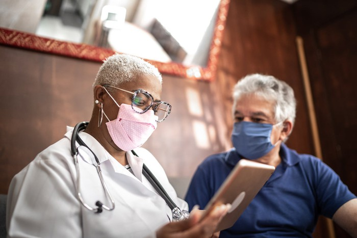 A doctor reviews results on a tablet with a patient.