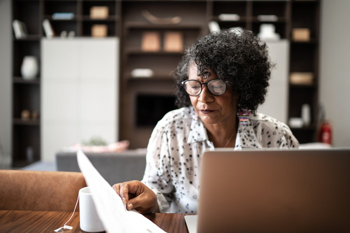 Older adult reviewing financial paperwork in front of computer.