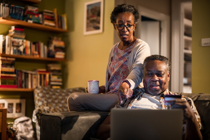 Two adults looking at a computer together.