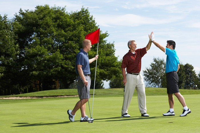Three people on golf course. One is holding the flag and the other two are giving a high-five.