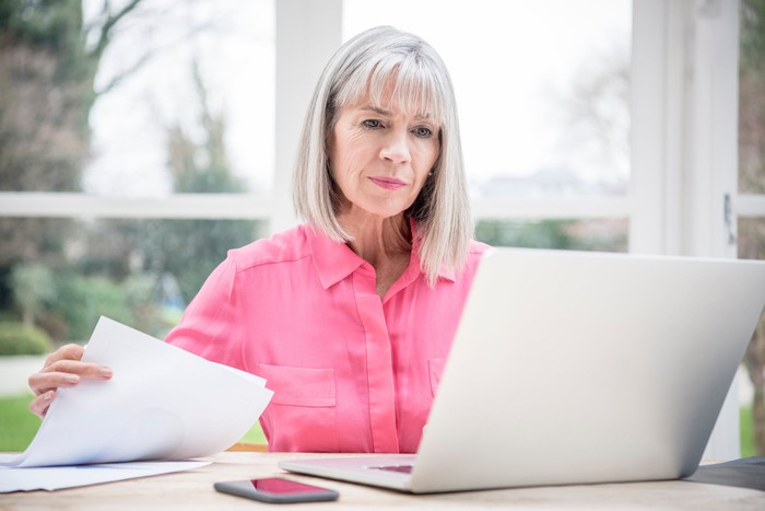 Serious senior holding document and looking at laptop
