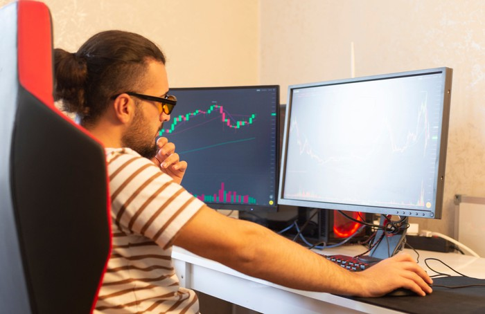 A person sits at their computer monitoring two screens, one of which shows a stock chart.