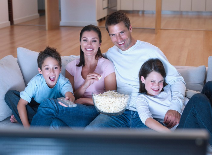 Une famille mange du pop-corn et regarde la télévision.