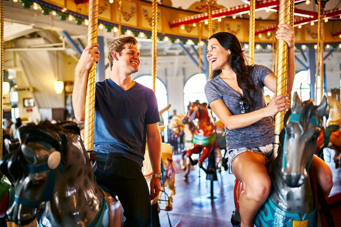 Two smiling people riding a carousel.