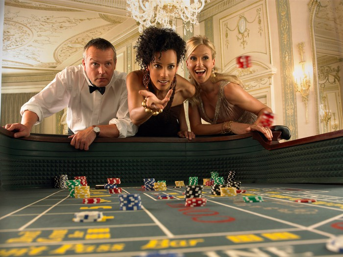 Three people at a craps table with dice rolling.
