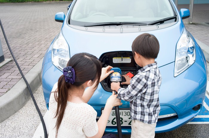 An adult and child charging an electric car at a charging station.