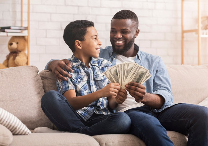 A person and child happily counting money.