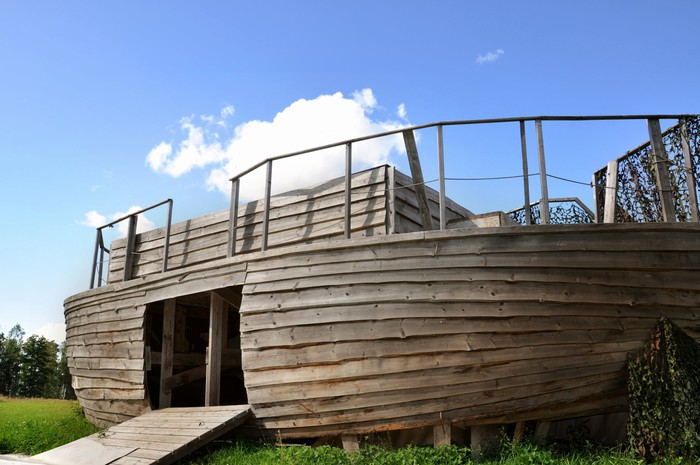 A wooden ark with an open door on land.