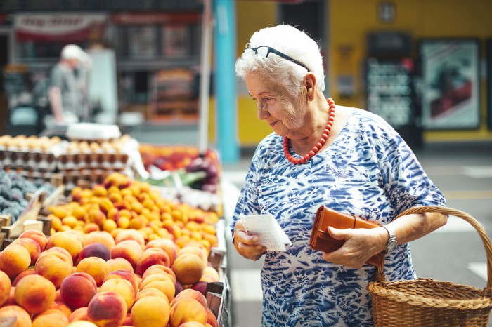 Shopper looking at fruit, holding list, wallet, and basket.