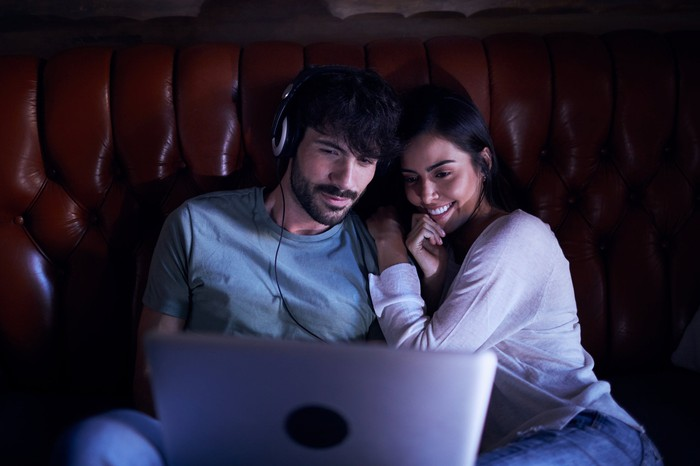 Couple on a couch watching a laptop PC.